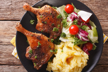baked duck leg, mashed potatoes and fresh salad mix close-up. horizontal top view