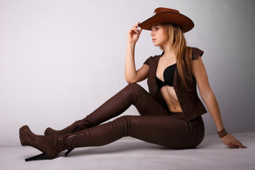 cowboy style. lifestyle. woman in leather pants.  grey background