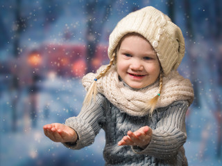 Wonderful little girl catches the falling snowflakes. The good, happy child's smile. Portrait