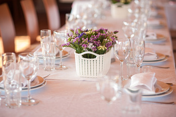 table setting in restaurant with flowers and wineglasses