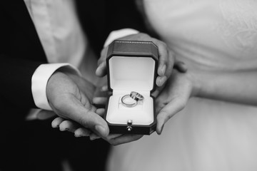 The bride and groom holding an open box with rings, a black and white image