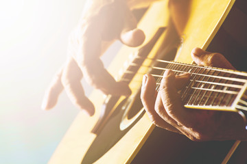 The old man's hand playing acoustic guitar