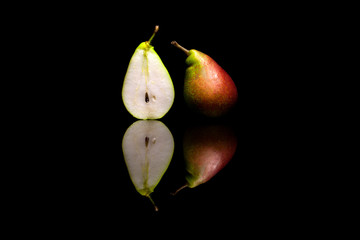 One cut in half and one whole red and green pears isolated on bl