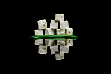 Eight blocks of feta cheese with whole green chive on black back