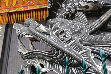 Head of a dragon carved out of stone. Dragon Head Black Stone Sculpture. The ornament outside the Xingtian Temple in Taipei, Taiwan.