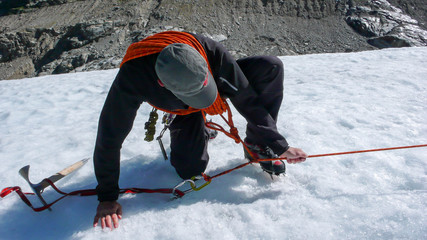 mountain guide demonstrating a crevasse rescue on a glacier in the Swiss Alps