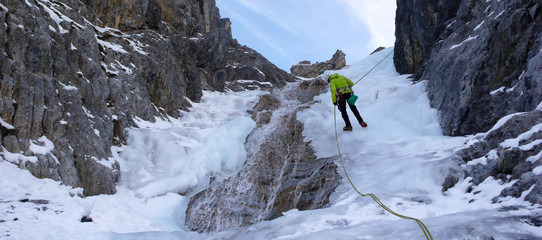 an ice climber rappelling on an ice fall in the Swiss Alps