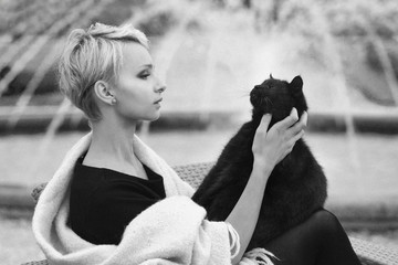 a beautiful blonde woman with a black cat, holding a black cat, stroking a cat