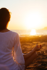 Young woman practicing morning yoga in nature at the beach. Copy space text.