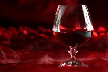 kieliszek brandy na czerwonym tle