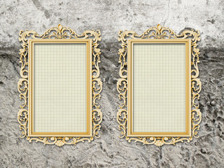 Two blank golden Baroque picture frames on rough gray wall background