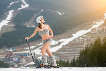 Beautiful naked woman skier is enjoying the spring sun on the top of the snowy slope. Wearing skis, boots, helmet and sunglasses. Spring is coming to the ski resort
