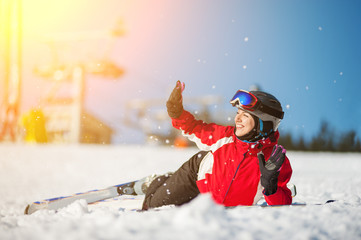 Smiling female skier lying with skis on snowy at mountain top in sunny day, having fun at a winter resort, ski lifts and blue sky in background