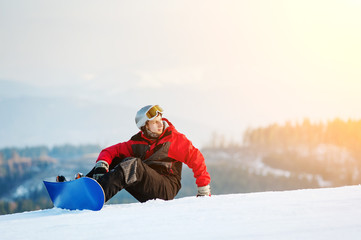 Snowboarder wearing helmet, red jacket, gloves and pants sitting on snowy slope on top of a mountain looking away, with an astonishing view on hills. Carpathian mountains