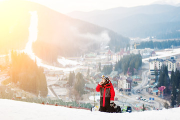 Male snowboarder sitting on ski slope, he's kneeling, looking away and talking on the phone, with an astonishing view on mountains and a small town located between the hills