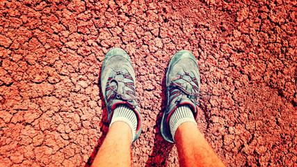 Legs in sneakers of man standing on cracked ground during summer