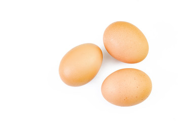 Three brown eggs isolated on white.