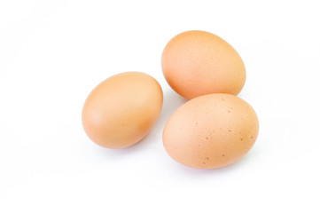 Three brown raw eggs isolated on white background