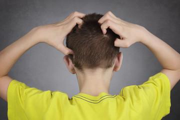 enfant garçon 14 ans se grattant la tête