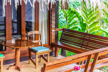 Vintage wooden chairs, benches and table on a home porch. They are traditional furnitures in Thailand, Asia.