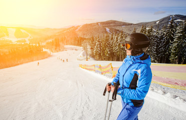 Side portrait of young cute woman skier looking at beautiful mountain landscape at the ski resort on a sunny day. Girl is wearing blue jacket helmet and goggles. Wide angle. Carpathian Mountains