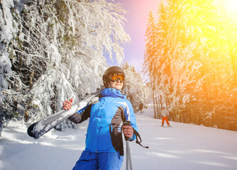 Portrait of young happy female skier on a ski slope in the winter forest on a sunny day. Woman is holding skis on her shoulder. Ski resort. Carpathian Mountains, Bukovel, Ukraine