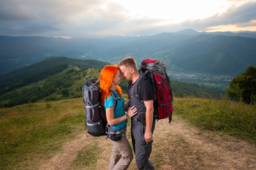 Man and red-haired woman standing facing each other and smiling on the road in the mountains on the background of the landscaped mighty mountains, forests, hills and cloudy sky