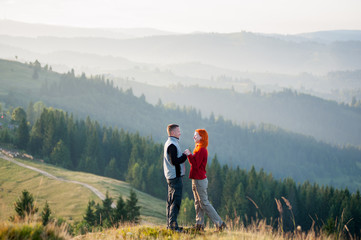 Happy guy and girl standing facing each other on a hill at the mountains in the morning. Lifestyle active vacations concept mountains and forests landscape on background