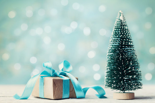 Miniature fir tree and christmas gift box against blue bokeh background. Holiday greeting card.