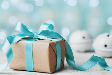 Christmas gift box and jingle bell against blue bokeh background. Holiday greeting card.