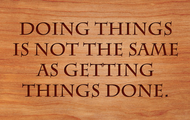 Doing things is not the same as getting things done - a quote on wooden red oak background