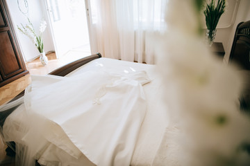 White Wedding dress on a bed, before ceremony