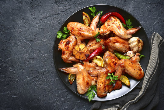 Grilled chicken wings on a black plate.Top view.