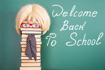 Woman teacher in front of blackboard with title WELCOME BACK TO