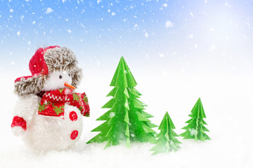 Christmas background, snowman with paper trees in the snow
