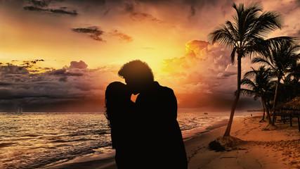 Silhouette di una coppia che si bacia in spiaggia al tramonto