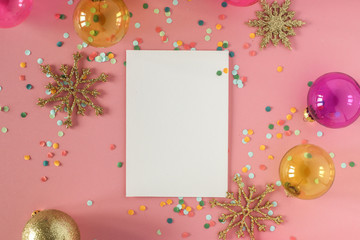 Mock up card on a pink background with their Christmas decorations and confetti. Invitation, card, paper. Place for text