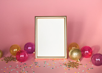 Gold picture frame with christmas ornaments. Mockup on pink background with confetti . Fashion decoration