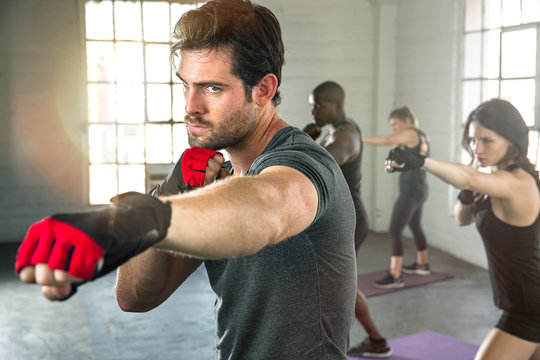 Intense focused man serious expression punching boxing workout throwing fist with group gym