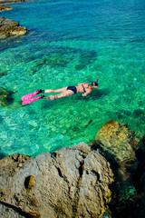 Schöne Frau im Bikini Schnorchelt durch Türkises Wasser an der Küste
