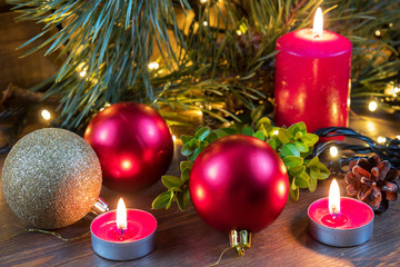 Light christmas candles and fir tree branch with lights decor and balls  on dark wooden background in vintage style. Coloring and processing photo