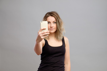 Young woman taking pictures through her phone
