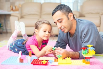Father And Little Daughter Playing With Toys Together At Home