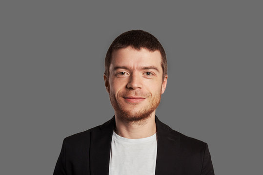30 years guy with little beard in casual wear have smile on the face. Stylish man in black jacket and white t-shirt on grey background. Boy look to the camera with fun emotion.