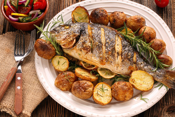 Photo sur Plexiglas Poisson Grilled fish with roasted potatoes and vegetables on the plate