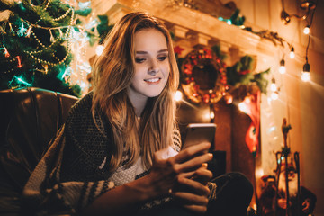 Portrait of a young smiling woman doing online shopping before christmas
