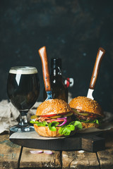 Homemade beef burgers with crispy bacon and fresh vegetables on serving board with glass of dark beer on rustic wooden table, dark blue plywood wall as background, copy space, vertical composition