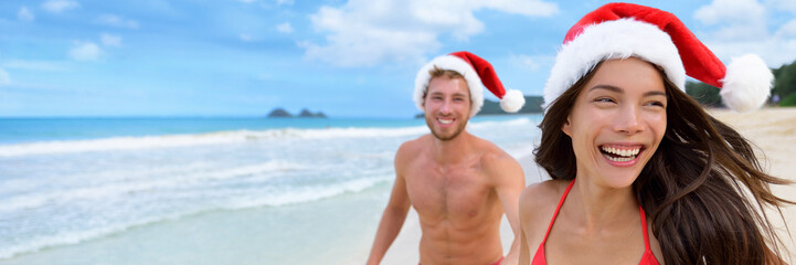 Happy Christmas holiday woman and man honeymoon couple laughing on beach vacation wearing santa claus hats carefree in freedom. Smiling Asian girl people lifestyle.