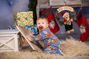 Christmas baby in sleepwear with dummy near gift boxes and christmas stockings