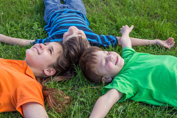 Three dreaming kids lying down on green grass